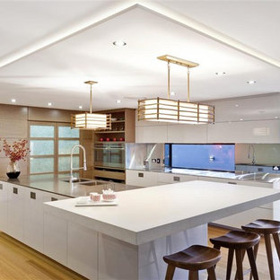 Example of a trendy kitchen design in Brisbane with stainless steel appliances and white countertops