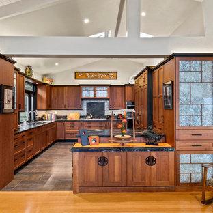 Новый формат декора квартиры: п-образная кухня в восточном стиле с врезной раковиной, фасадами цвета дерева среднего тона, фартуком из каменной плиты, техникой под мебельный фасад, фасадами в стиле шейкер, черным фартуком, полуостровом, серым полом и черной столешницей