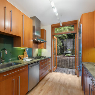 This is an example of a small asian galley separate kitchen in San Francisco with a single-bowl sink, flat-panel cabinets, light wood cabinets, marble benchtops, green splashback, glass sheet splashback, stainless steel appliances, light hardwood floors, no island, beige floor and green benchtop.