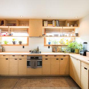Cette image montre une cuisine asiatique en U avec un évier encastré, un placard à porte plane, des portes de placard en bois clair, un plan de travail en bois, une crédence blanche, un électroménager en acier inoxydable, béton au sol, aucun îlot, un sol gris et un plan de travail marron.