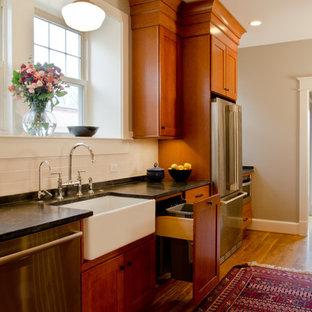 Inspiration for a large traditional galley separate kitchen in DC Metro with a farmhouse sink, shaker cabinets, medium wood cabinets, granite benchtops, white splashback, ceramic splashback, stainless steel appliances, light hardwood floors and no island.