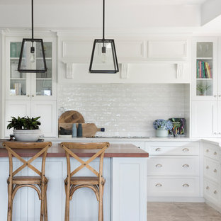 Large traditional l-shaped kitchen in Other with shaker cabinets, white cabinets, white splashback, an island, beige floor, white benchtop and subway tile splashback.