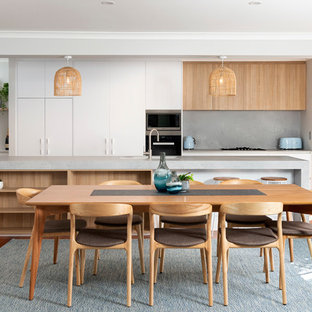 This is an example of a contemporary galley eat-in kitchen in Perth with an undermount sink, flat-panel cabinets, white cabinets, grey splashback, stainless steel appliances, medium hardwood floors, with island, brown floor and grey benchtop.