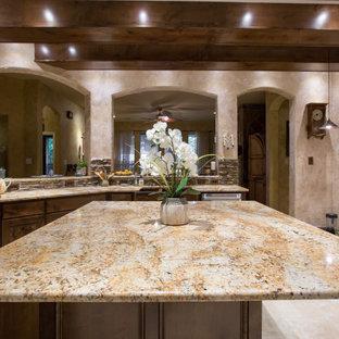 Geschlossene, Große Klassische Küche in U-Form mit Landhausspüle, profilierten Schrankfronten, dunklen Holzschränken, Granit-Arbeitsplatte, bunter Rückwand, Rückwand aus Steinfliesen, Küchengeräten aus Edelstahl, Teppichboden, Kücheninsel, grauem Boden und brauner Arbeitsplatte in Dallas