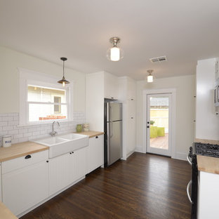 Photo of a mid-sized arts and crafts u-shaped eat-in kitchen in Los Angeles with a peninsula, beaded inset cabinets, white cabinets, wood benchtops, white splashback, subway tile splashback, stainless steel appliances, a farmhouse sink and dark hardwood floors.