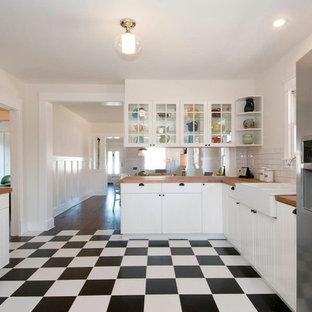 Idéer för mellanstora amerikanska kök, med en halv köksö, luckor med profilerade fronter, vita skåp, träbänkskiva, vitt stänkskydd, stänkskydd i tunnelbanekakel, rostfria vitvaror, en rustik diskho och klinkergolv i keramik