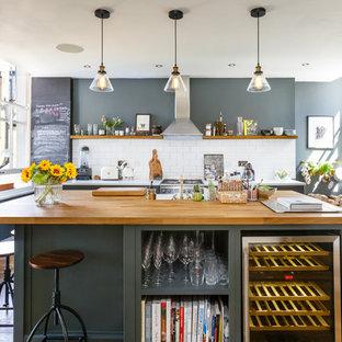 Photo of a scandi kitchen in London with white splashback, metro tiled splashback, stainless steel appliances, medium hardwood flooring, an island, brown floors and white worktops.