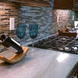 マイアミの中サイズの地中海スタイルのおしゃれなキッチン (ダブルシンク、レイズドパネル扉のキャビネット、濃色木目調キャビネット、ソープストーンカウンター、マルチカラーのキッチンパネル、ボーダータイルのキッチンパネル、シルバーの調理設備の、淡色無垢フローリング) の写真
