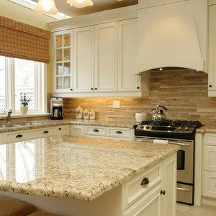 Mittelgroße Klassische Küche in U-Form mit Granit-Arbeitsplatte, Doppelwaschbecken, Schrankfronten mit vertiefter Füllung, weißen Schränken, Küchenrückwand in Braun, Küchengeräten aus Edelstahl, Rückwand aus Steinfliesen, Keramikboden und Kücheninsel in Toronto
