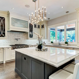 Photo of a transitional l-shaped kitchen in Toronto with an undermount sink, glass-front cabinets, beige cabinets, grey splashback, stainless steel appliances, dark hardwood floors, with island, brown floor and white benchtop.