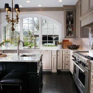 Exempel på ett mellanstort klassiskt l-kök, med luckor med glaspanel, en undermonterad diskho, beige skåp, granitbänkskiva, vitt stänkskydd, stänkskydd i stenkakel, rostfria vitvaror och mörkt trägolv