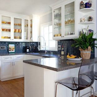 Small traditional kitchen ideas - Small elegant u-shaped medium tone wood floor kitchen photo in Los Angeles with glass-front cabinets, a peninsula and blue backsplash