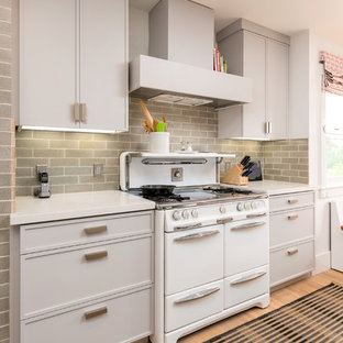 Small eclectic eat-in kitchen pictures - Eat-in kitchen - small eclectic l-shaped medium tone wood floor eat-in kitchen idea in San Francisco with a drop-in sink, recessed-panel cabinets, gray cabinets, quartz countertops, green backsplash, ceramic backsplash, white appliances and an island