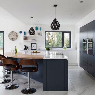 Inspiration för ett funkis kök, med släta luckor, svarta skåp, vitt stänkskydd, svarta vitvaror och en köksö