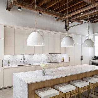 ニューヨークの広いコンテンポラリースタイルのおしゃれなキッチン (アンダーカウンターシンク、フラットパネル扉のキャビネット、白いキャビネット、大理石カウンター、白いキッチンパネル、大理石のキッチンパネル、パネルと同色の調理設備、コンクリートの床、グレーの床、白いキッチンカウンター) の写真