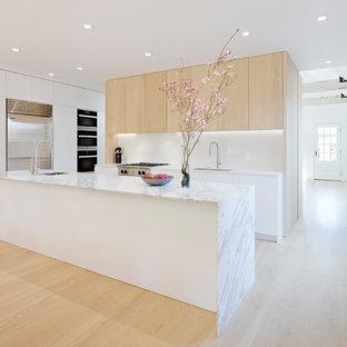Offene, Zweizeilige, Mittelgroße Moderne Küche mit Unterbauwaschbecken, flächenbündigen Schrankfronten, hellen Holzschränken, Marmor-Arbeitsplatte, Küchenrückwand in Weiß, Küchengeräten aus Edelstahl, hellem Holzboden, Kücheninsel, beigem Boden, Glasrückwand und grauer Arbeitsplatte in San Francisco
