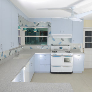 Photo of a mid-sized midcentury u-shaped eat-in kitchen in Miami with an integrated sink, flat-panel cabinets, laminate benchtops, glass tile splashback, blue cabinets, beige splashback, linoleum floors, no island and beige floor.