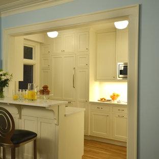 Foto de cocina de galera, de estilo americano, pequeña, cerrada, con armarios estilo shaker, puertas de armario blancas, encimera de cuarzo compacto, salpicadero blanco, salpicadero de azulejos tipo metro, electrodomésticos de acero inoxidable y suelo de madera clara