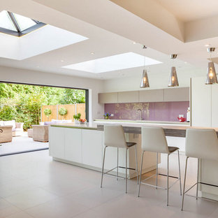Photo of a contemporary galley kitchen/diner in Oxfordshire with flat-panel cabinets, white cabinets, glass sheet splashback, an island, grey floors and white worktops.