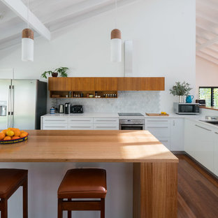 This is an example of a contemporary l-shaped kitchen in Brisbane with a double-bowl sink, flat-panel cabinets, white cabinets, white splashback, mosaic tile splashback, stainless steel appliances, with island and medium hardwood floors.