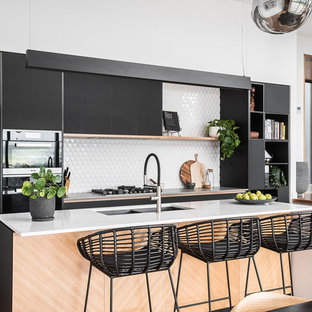 Photo of a contemporary kitchen in Hobart with a double-bowl sink, flat-panel cabinets, black cabinets, white splashback, stainless steel appliances, medium hardwood floors, with island, brown floor and white benchtop.
