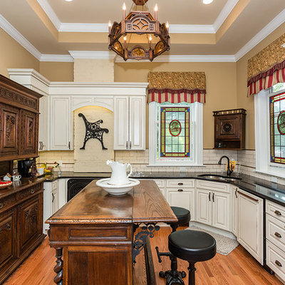 Example of a classic medium tone wood floor kitchen design in St Louis with a double-bowl sink, raised-panel cabinets, white cabinets, white backsplash, subway tile backsplash, stainless steel appliances, an island and black countertops