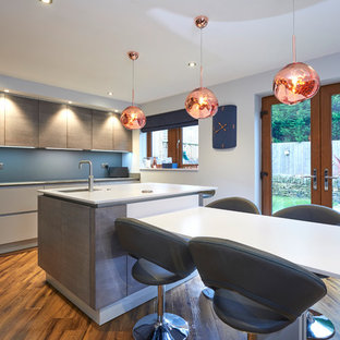 Design ideas for a contemporary galley kitchen/diner in Other with a submerged sink, flat-panel cabinets, grey cabinets, blue splashback, medium hardwood flooring, an island, brown floors and white worktops.