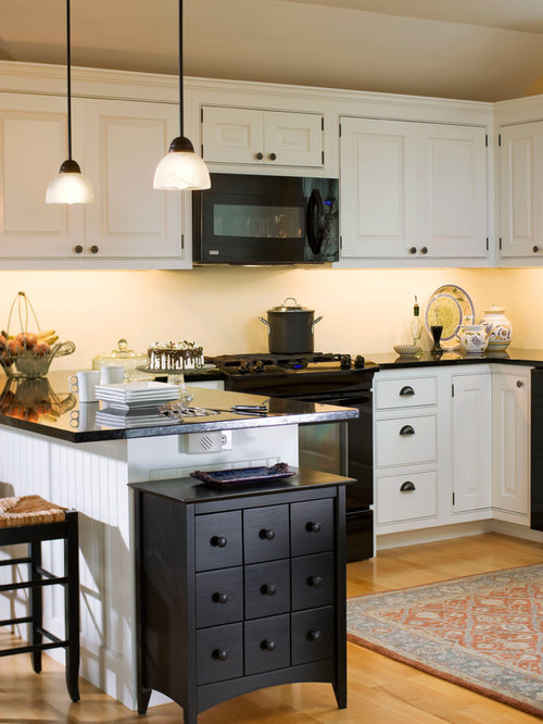 black and white kitchen design pictures. farmhouse kitchen idea in burlington with white cabinets, black appliances and beaded inset cabinets design pictures