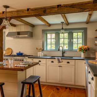 Mid-sized farmhouse eat-in kitchen inspiration - Mid-sized cottage l-shaped medium tone wood floor eat-in kitchen photo in Boston with an undermount sink, shaker cabinets, white cabinets, granite countertops, gray backsplash, ceramic backsplash, stainless steel appliances, an island and black countertops