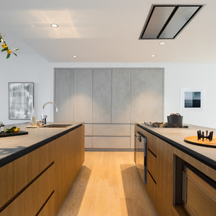 Inspiration for a large contemporary u-shaped open plan kitchen in New York with an undermount sink, flat-panel cabinets, medium wood cabinets, concrete benchtops, stainless steel appliances, light hardwood floors and multiple islands.