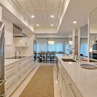 Design ideas for a small nautical galley kitchen in Miami with a single-bowl sink, white splashback, stone tiled splashback, stainless steel appliances, an island, beige floors, yellow worktops, recessed-panel cabinets, white cabinets and porcelain flooring.