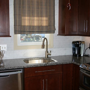 Design ideas for a mid-sized traditional l-shaped eat-in kitchen in Providence with no island, shaker cabinets, dark wood cabinets, granite benchtops, grey splashback, porcelain splashback, stainless steel appliances, an undermount sink and medium hardwood floors.