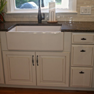 Large traditional eat-in kitchen remodeling - Inspiration for a large timeless u-shaped medium tone wood floor eat-in kitchen remodel in Providence with an island, raised-panel cabinets, beige cabinets, granite countertops, beige backsplash, ceramic backsplash, white appliances and a farmhouse sink