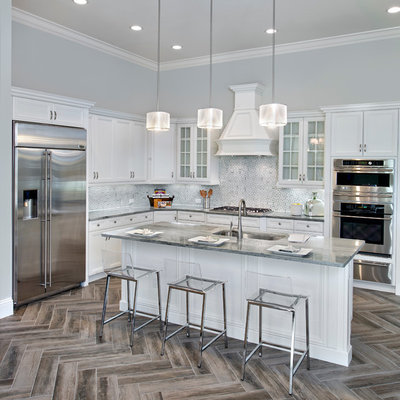 Example of a transitional l-shaped kitchen design in Tampa with an undermount sink, recessed-panel cabinets, white cabinets, multicolored backsplash, stainless steel appliances and an island
