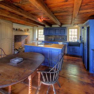 Diseño de cocina comedor en L, rural, de tamaño medio, con armarios con paneles con relieve, puertas de armario azules, fregadero sobremueble, encimera de madera, salpicadero azul, electrodomésticos con paneles, suelo de madera oscura, una isla y salpicadero de pizarra