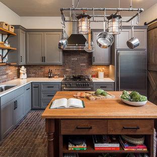 Lantlig inredning av ett avskilt, stort l-kök, med en undermonterad diskho, skåp i shakerstil, grå skåp, rostfria vitvaror, tegelgolv, en köksö och stänkskydd i tegel