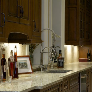 Contemporary eat-in kitchen pictures - Trendy galley eat-in kitchen photo in St Louis with stainless steel appliances, an undermount sink, raised-panel cabinets, dark wood cabinets, beige backsplash, granite countertops and stone tile backsplash