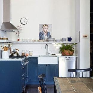 ニューヨークのインダストリアルスタイルのおしゃれなキッチン (エプロンフロントシンク、シェーカースタイル扉のキャビネット、青いキャビネット、白いキッチンパネル、サブウェイタイルのキッチンパネル、シルバーの調理設備の、濃色無垢フローリング、アイランドなし、茶色い床、グレーのキッチンカウンター) の写真