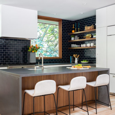 Kitchen - mid-century modern light wood floor, brown floor and vaulted ceiling kitchen idea in San Francisco with an undermount sink, flat-panel cabinets, white cabinets, concrete countertops, blue backsplash, ceramic backsplash, paneled appliances and gray countertops