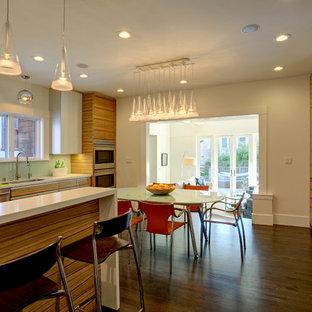 サンフランシスコの大きいモダンスタイルのおしゃれなキッチン (ドロップインシンク、フラットパネル扉のキャビネット、淡色木目調キャビネット、クオーツストーンカウンター、緑のキッチンパネル、ガラス板のキッチンパネル、シルバーの調理設備の、濃色無垢フローリング) の写真