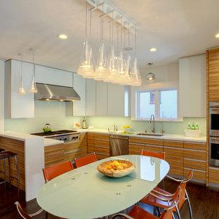 サンフランシスコの大きいモダンスタイルのおしゃれなキッチン (ドロップインシンク、フラットパネル扉のキャビネット、淡色木目調キャビネット、クオーツストーンカウンター、緑のキッチンパネル、ガラス板のキッチンパネル、シルバーの調理設備、濃色無垢フローリング) の写真