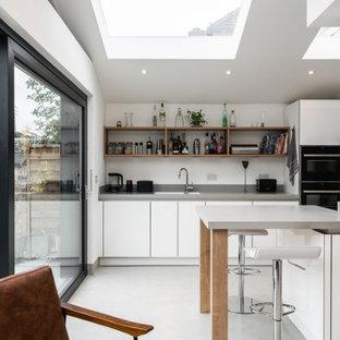 Imagen de cocina actual, abierta, con armarios con paneles lisos, puertas de armario blancas, electrodomésticos negros, una isla, suelo gris y encimeras grises