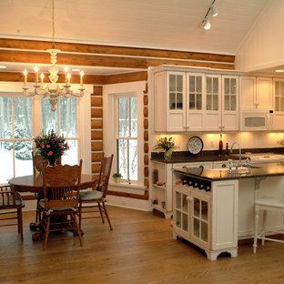 Inspiration pour une cuisine américaine chalet en L avec un placard à porte vitrée, des portes de placard blanches, une crédence blanche et un électroménager encastrable.