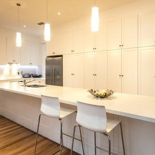 Design ideas for a transitional l-shaped kitchen in Adelaide with a double-bowl sink, shaker cabinets, white cabinets, stainless steel appliances, medium hardwood floors, an island, brown floor and white benchtop.