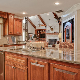 Design ideas for a large arts and crafts l-shaped kitchen pantry in Dallas with a double-bowl sink, raised-panel cabinets, medium wood cabinets, granite benchtops, beige splashback, ceramic splashback, stainless steel appliances, terra-cotta floors and with island.