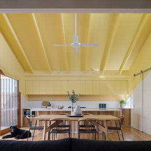 Imagen de cocina de galera, contemporánea, abierta, con armarios con paneles lisos, puertas de armario amarillas, salpicadero amarillo, salpicadero de azulejos tipo metro, suelo de madera en tonos medios, una isla y suelo marrón