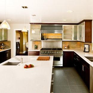 Modelo de cocina contemporánea con salpicadero de azulejos en listel, electrodomésticos de acero inoxidable, fregadero de doble seno, armarios tipo vitrina, puertas de armario en acero inoxidable y salpicadero amarillo