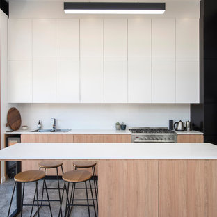 Inspiration for a mid-sized modern single-wall eat-in kitchen in Newcastle - Maitland with flat-panel cabinets, white splashback, stainless steel appliances, concrete floors, an island, grey floor, white benchtop, a double-bowl sink and white cabinets.