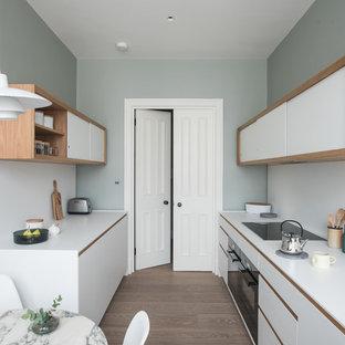 Diseño de cocina comedor de galera, contemporánea, pequeña, sin isla, con fregadero integrado, puertas de armario blancas, encimera de acrílico, salpicadero blanco, electrodomésticos negros, suelo de madera en tonos medios, encimeras blancas y armarios con paneles lisos