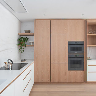 Design ideas for a medium sized modern l-shaped kitchen in London with an integrated sink, flat-panel cabinets, light wood cabinets, white splashback, black appliances, light hardwood flooring, no island, beige floors and white worktops.